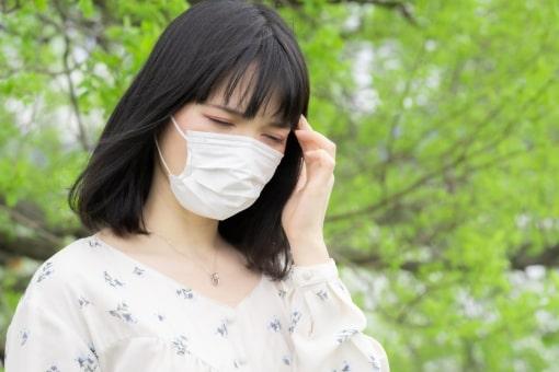 マスクをしている女性が頭を抑えている